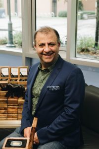 A portrait Dr. Tafazoli seated among the 100 Rhino Gold bars he purchased for Motion Metrics.