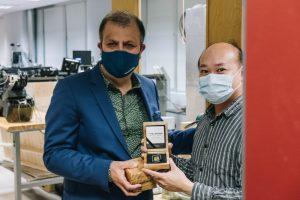 Dr. Tafazoli handing a Rhino Gold bar to a masked employee.